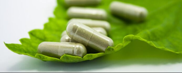 Health supplement capsules resting on a green leaf